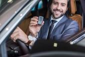 mosolygó üzletember a autó kulcs új autót szalon forgalmazási készpénzkészlet ül portréja