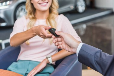 partial view of dealership salon seller giving car key to smiling woman in auto salon