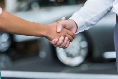 cropped shot of dealership salon shop assistant and female customer shaking hands in auto salon