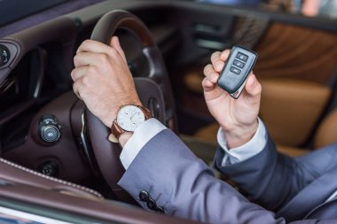 cropped shot of businessman with car key in hand sitting in new car in dealership salon