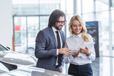 female auto salon seller with tablet helping smiling businessman to choose car at dealership salon