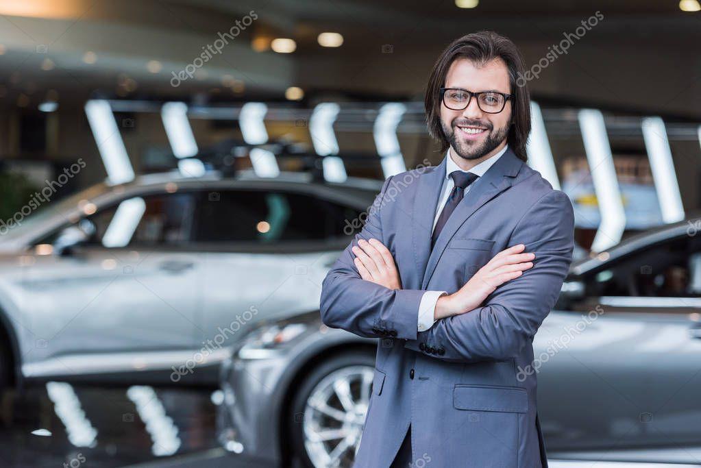 uomo d'affari sorridente con le braccia incrociate in piedi nel salone di concessionaria con auto nuove sullo sfondo
