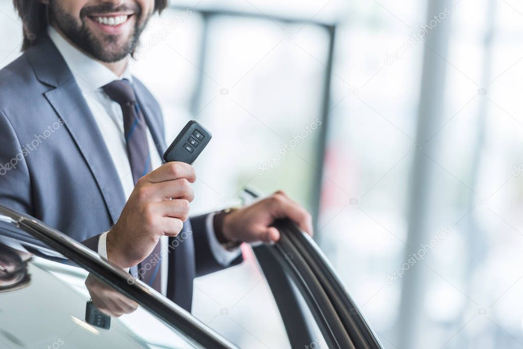 Cropped shot of smiling businessman with car key standing at new car at dealership salon
