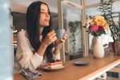 Fotografia giovane donna pensierosa con tazza di caffè seduti al tavolo con cheesecake in caffè