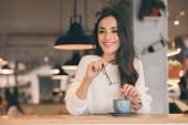 usměvavá mladá žena držící brýle zatímco sedí u stolu s šálek kávy v kavárně