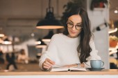 atraktivní mladá žena v brýlích, čtení knihy u stolu s šálek kávy v kavárně