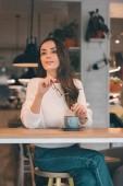 krásná mladá žena odvrátila a podržíte brýle a sedí u stolu s šálek kávy v kavárně