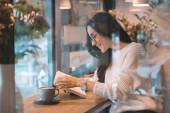 usmívající se žena čtení knih u stolu s šálek kávy v kavárně