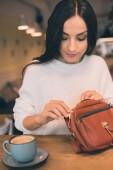 atraktivní žena vytáhne peníze z vaku u stolu s šálek kávy v kavárně