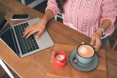 cropped image of female freelancer working on laptop while sitting at table with smartphone and coffee cup in cafe