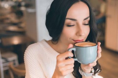 close up portrait of young woman with closed eyes drinking coffee in cafe