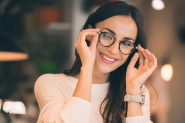 portrait of happy attractive woman taking off eyeglasses in cafe
