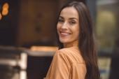 Selektivní fokus krásné stylové ženy při pohledu na fotoaparát na městské ulici