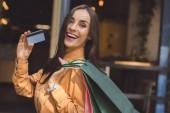 Fotografie Módní usmívající se žena s nákupní tašky ukazující kreditní karty na městské ulici