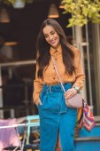 happy fashionable young woman with stylish handbag at urban street