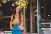 Photo smiling fashionable young woman with stylish handbag at urban street