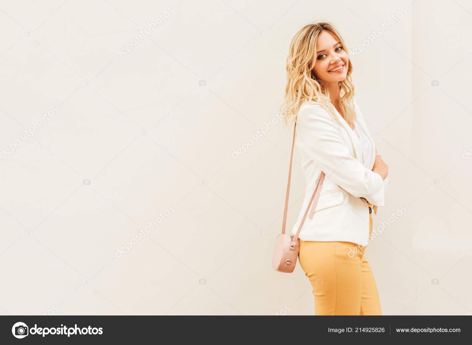 Sonriente a mujer hermosa elegante en traje de otoño de pie junto a la  pared beige en la ciudad y mirando a cámara — Foto de AllaSerebrina f6ce947688e4