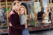 usmíval se milující pár v podzimní oblečení objímání poblíž kolotoč v zábavním parku a hledat dál