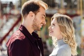 portrait of affectionate couple in autumn outfit looking at each other near carousel in amusement park