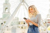 Photo beautiful smiling woman in autumn outfit using smartphone near observation wheel in city