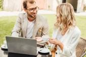 usmívající se pár v podzimní oblečení sedí u stolu s notebookem a pití kávy v kavárně