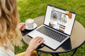 cropped image of woman using laptop with loaded bbc food page on table in garden