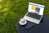 přenosný počítač s načtené rezervační stránku, šálek kávy a smartphone s prázdnou obrazovkou na stole v zahradě