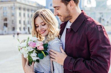 handsome boyfriend hugging attractive girlfriend with bouquet in city