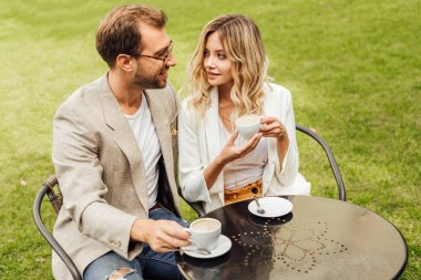 architecture couple in autumn outfit sitting at table in cafe with coffee and looking at each other