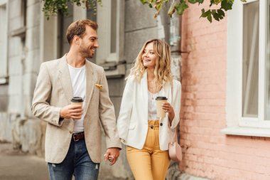 smiling couple in autumn outfit holding hands, looking at each other and walking on street with disposable coffee cups