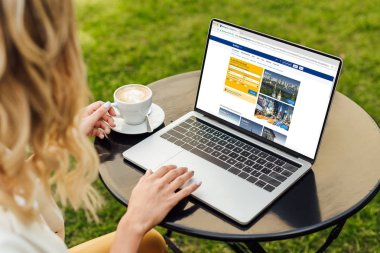 cropped image of woman using laptop with loaded booking page on table in garden