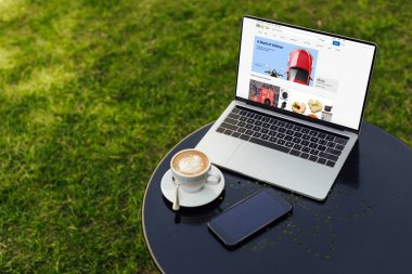 laptop with loaded ebay page, cup of cappuccino and smartphone on table in garden
