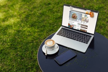 laptop with loaded bbc food page, cup of coffee and smartphone with blank screen on table in garden