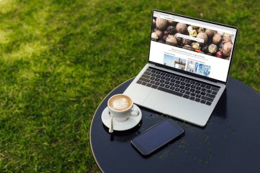 laptop with loaded depositphotos page and smartphone on table in garden
