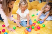 Fotografie educator gesturing on colored balls to kids in kindergarten, child pointing on one