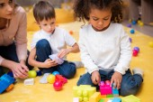 upset african american child playing with colored constructor in kindergarten