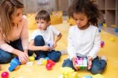 Fotografie pedagog a multietnickou děti hrát s plastovými konstruktor ve školce