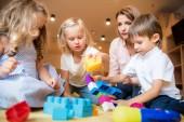 Fotografie hladinou učitele a děti si hrají s konstruktor ve školce