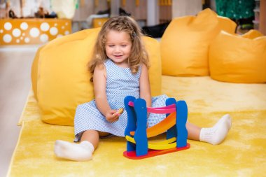 happy adorable child sitting on carpet and playing with toy in kindergarten