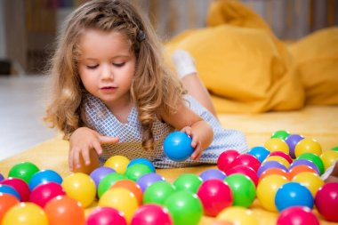 adorable child lying on carpet and playing with colorful balls in kindergarten