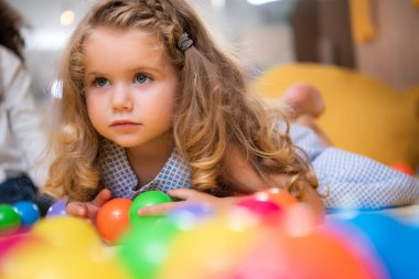 adorable child lying on carpet with colorful balls in kindergarten and looking away