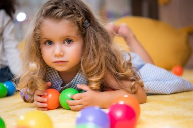 adorable child lying on carpet with colorful balls in kindergarten and looking at camera