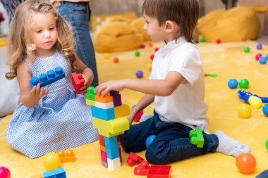 Adorable children playing with constructor in kindergarten stock vector