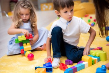 male and female kids playing with constructor in kindergarten