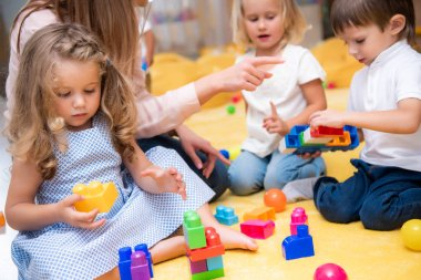 cropped image of educator pointing on something to kids playing with constructor in kindergarten
