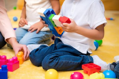cropped image of tutor and kids playing with constructor in kindergarten