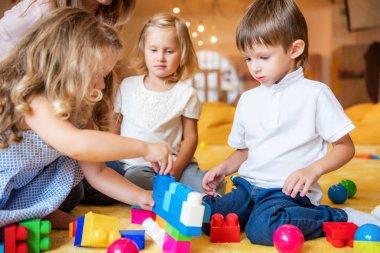 Adorable kids playing with constructor on floor in kindergarten stock vector
