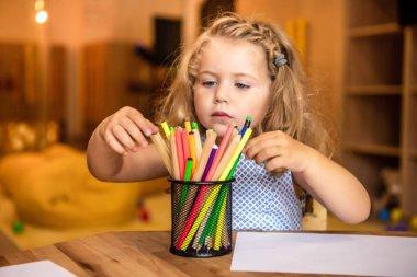 Adorable child choosing felt tip pen for drawing in kindergarten stock vector