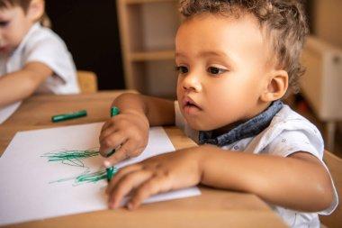adorable african american boy drawing with green felt tip pen in kindergarten