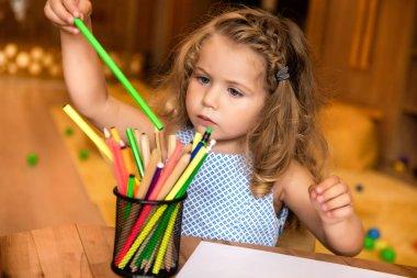 Adorable child taking green felt tip pen for drawing in kindergarten stock vector